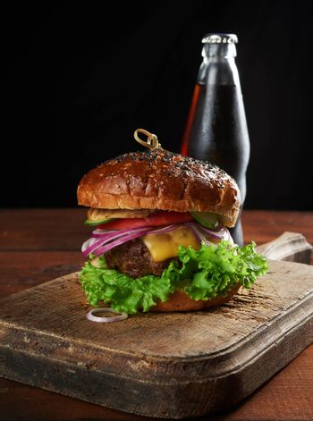 delicious burger with fried beef cutlet and onions. crispy white wheat flour bun with sesame seeds. Fast food on a wooden board, behind a bottle with a drink