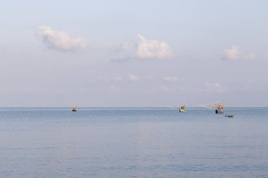 Sea with fishing boats and blue sky