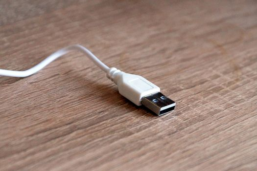 white usb cable on a wooden table close-up