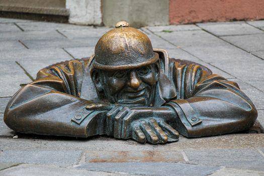 Bratislava, Slovakia - July 5th 2020: The 'Man at Work' statue called Cumil, in Bratislava's old town, Slovakia