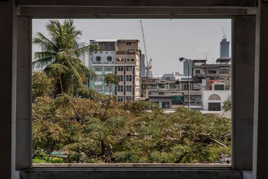 View of buildings and big trees in Bangkok. Looks through the window frames in abandoned building. Selective focus.