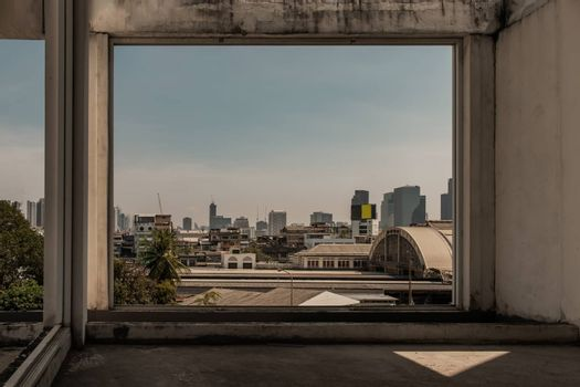 Roof of Hua Lamphong Station And the sky background of Bangkok. Looks through the window frames in abandoned building. No focus, specifically.
