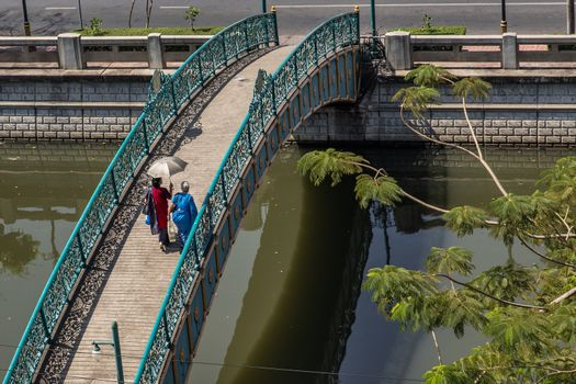 Two indian woman in traditional attire walking on a bridge over a small canal. Selective focus.