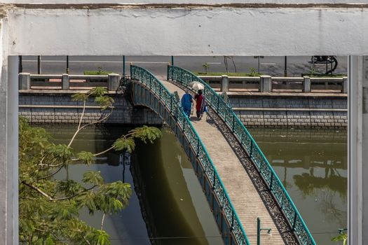 Two indian woman in traditional attire walking on a bridge over a small canal. looks through the window frames in abandoned building. Selective focus.