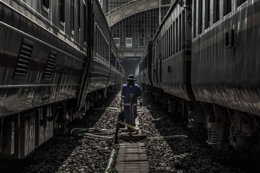 Cleaning staff while cleaning the train at Bangkok Railway Station or Hua Lamphong Railway Station. Focus and blur.