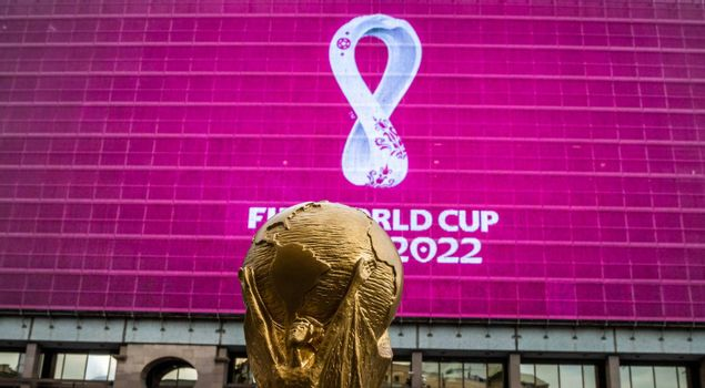 4 September 2019, Moscow, Russia. Copy of world cup trophy on background logo of the FIFA world Cup 2022, which will be held in Qatar, on a giant screen in the city center.