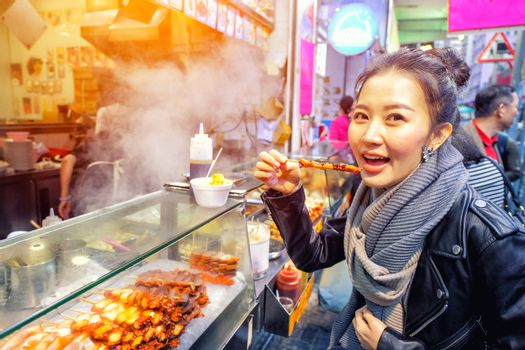 Chinese Asian young female model eating Grilled octopus on Street in Hong Kong