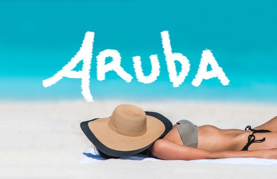ARUBA title written on sky above beach travel bikini suntan woman sleeping relaxing covering face with hat doing siesta. ARUBA text in blue ocean copyspace above. Summer and sun vacation holidays.