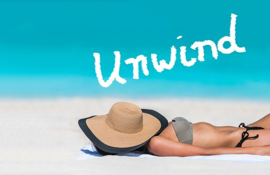 UNWIND word written on sky above beach travel bikini suntan woman sleeping relaxing covering face with hat doing siesta. UNWIND text in blue ocean copyspace above. Summer and sun vacation holidays.