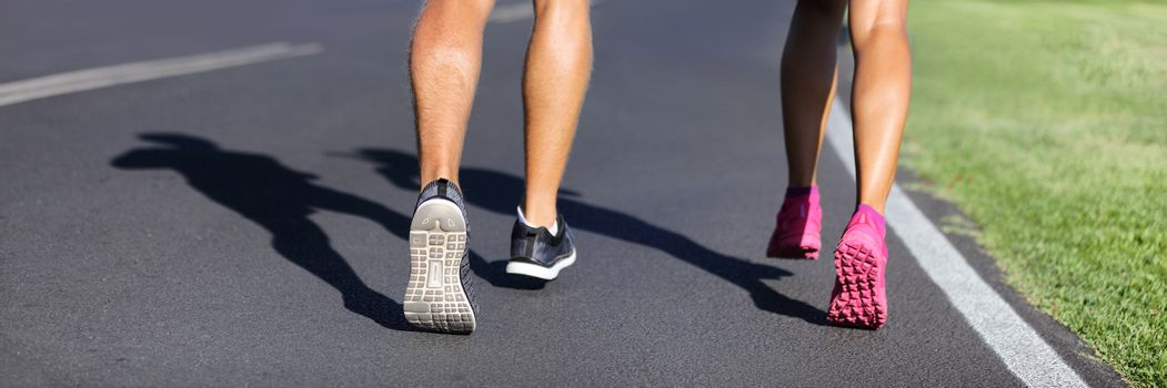 Fitness runners running road to weight loss banner - couple of young people jogging together - crop of legs and running shoes.