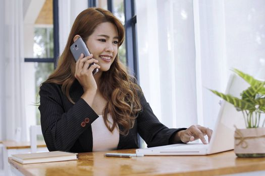 Business women use smartphones Sit on the table in the office modern.