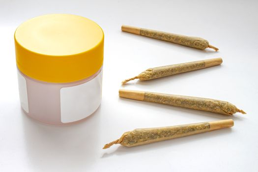 A Cannabis white and yellow plastic packaging container with Cigarettes, Prerolls or Joints and a on a white background