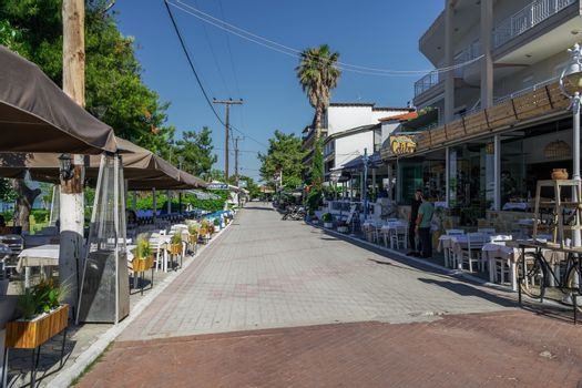 Restaurant personnel next to outdoor seating area without tourists in Hanioti, Kassandra peninsula.