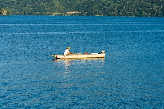 Man in boat relaxing and fishing on Danube river on a sunny day in Orsova, Romania, 2020.
