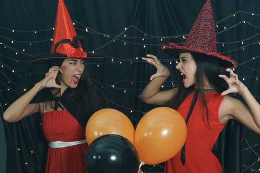 Beautiful woman and friend in Halloween devil costume and wearing witch hat. Have fun at nightclub party, decorate the lights by doing a scary face. Halloween celebration