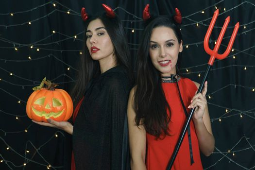 Beautiful woman and friend in Halloween devil costume with carved pumpkin and holy spear. Have fun at a party in a nightclub decorated with lights. Halloween celebration