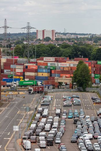 Southampton port, England, UK - June 08, 2020: Parking lot full of cars in the port of Southampton. Shipping containers in the background.