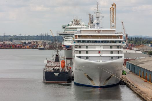 Southampton port, England, UK - June 08, 2020: Silver Spirit cruise ship docked in Southampton port and being refueled by fueling ship Whitonia. Some other cruise ship in the background.