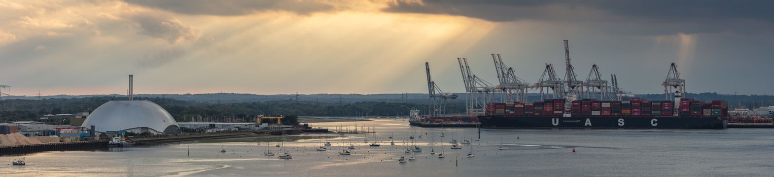 Southampton port, England, UK - June 08, 2020: Aerial panoramic view of Southampton port at sunset. Golden hour. Massive container ship UASC being loaded; yacht lot, metal factory dome in the middle
