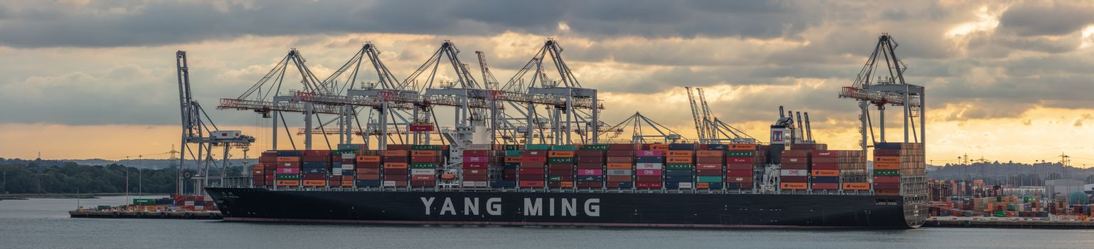 Southampton, UK - June 11, 2020: Panoramic aerial view of huge container ship Yang Ming being loaded with containers in the port of Southampton at sunset. Golden hour.