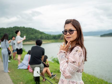 Phetchaburi, Thailand - 16 August 2020 Editorial illustrations. Thai women stand to take pictures at the dam ridge With a lot of people visiting this place.