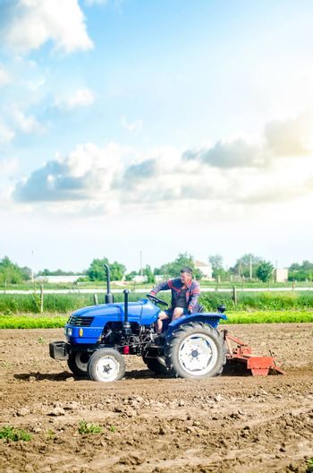The farmer drives a tractor with a milling unit equipment. Loosening land cultivation Use of agricultural machinery to speed up work. Farming. Plowing field. The stage of preparing soil for planting.