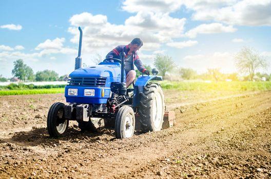 Farmer on a tractor loosens the soil with milling equipment. Loosening surface, land cultivation Use of agricultural machinery and to simplify and speed up work. Farming, agriculture. Plowing field.