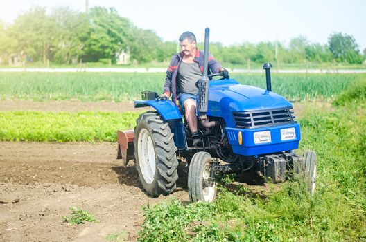 A farmer drives a tractor while working on a farm field. Loosening surface, cultivating the land. Farming, agriculture. Field preparation. Use of agricultural machinery and equipment to speed up work.