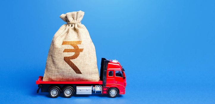 Truck is carrying a huge indian rupee money bag. Great investment. Attracting large funds to the economy for subsidies, support and cheap soft loans for businesses. Anti-crisis measures of government.
