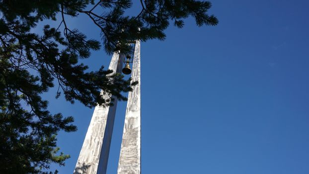 War memorial with a bell against a blue sky. Pine branches