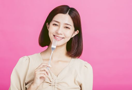 Beautiful young woman holding a fork and tasting food
