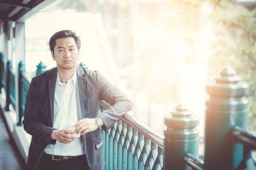 businessman asian handsome 30s wear suit standing outdoor hand h