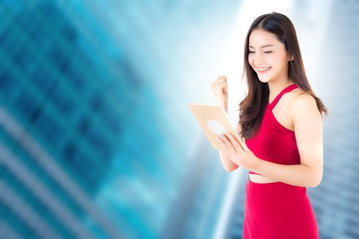 Young beautiful asian woman wear red dress looking on tablet with happy and success gesture glad on city background - communication business concept.