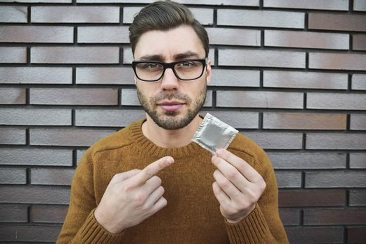 Male youngster with appealing look, holds condom.