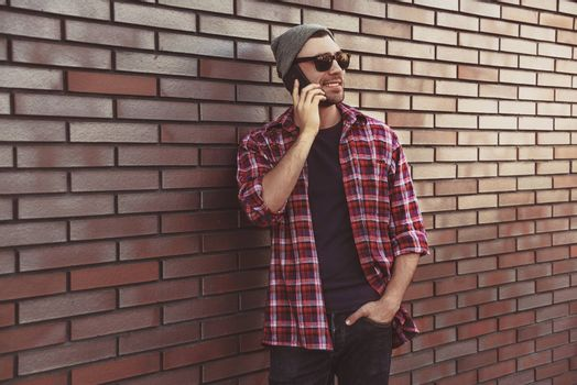 Hipster calling in city street on brick wall background. Amazing man holding smartphone in smart casual wear standing. Urban young professional lifestyle.