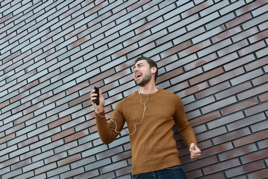Portrait of smiling man with headphones and cellphone standing by brick wall.