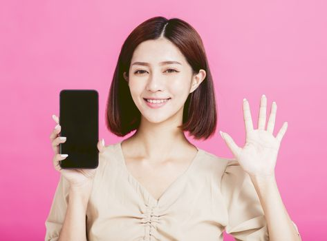Smiling young woman showing the smart phone