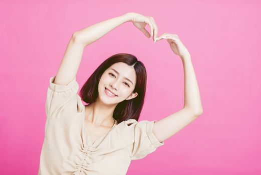 smiling young woman with heart shape gesture