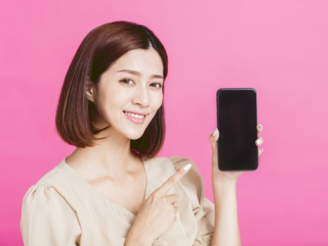 Smiling young woman showing and  pointing to smart phone