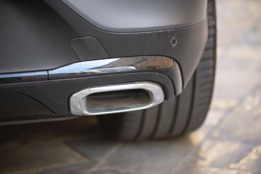 detail of a chrome exhaust of a parked sports car