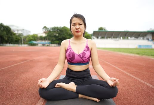 Asian young women doing yoga, stretching for a healthy body, healthy body at the outdoor sports stadium.