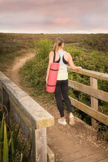 Woman in sportswear with a pink mat walks after training in the park at sunset