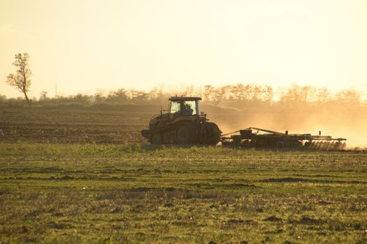 Tractor at sunset plow plow a field. Tilling the soil in the fall after harvest. The end of the season.