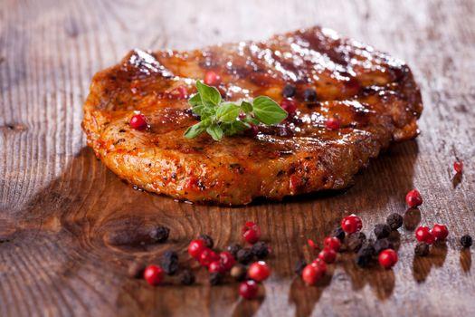 pork steak with pepper corns on wood