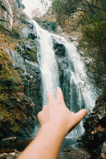Out of focus hand reaching to a majestic waterfall