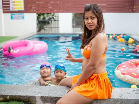 Portrait of mothers in swimsuits and their children play in the pool.