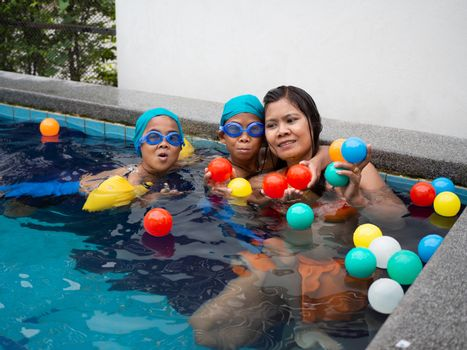 A portrait of a mother and son playing ball in the pool.