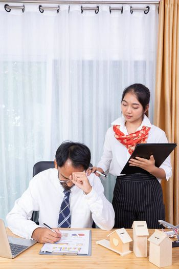 A businessman is frastrate on his business while his female assisstance touch to cheer him up