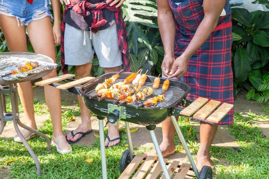 Man cooking meat on barbecue grill for house backyard party