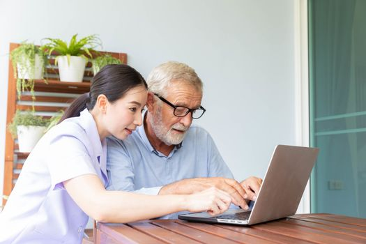 Nurse help senior retirement man working with laptop at home and feeling happy